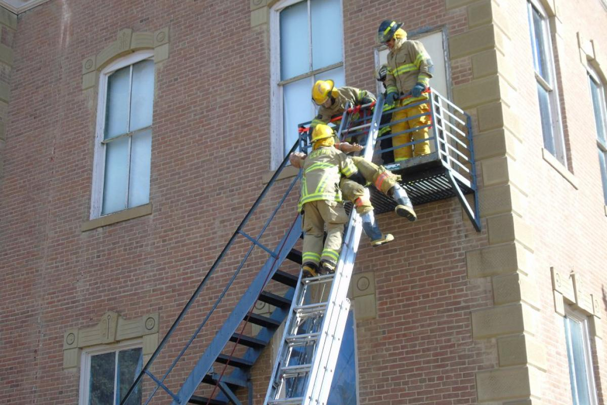 Firefighter carries dummy on ladder