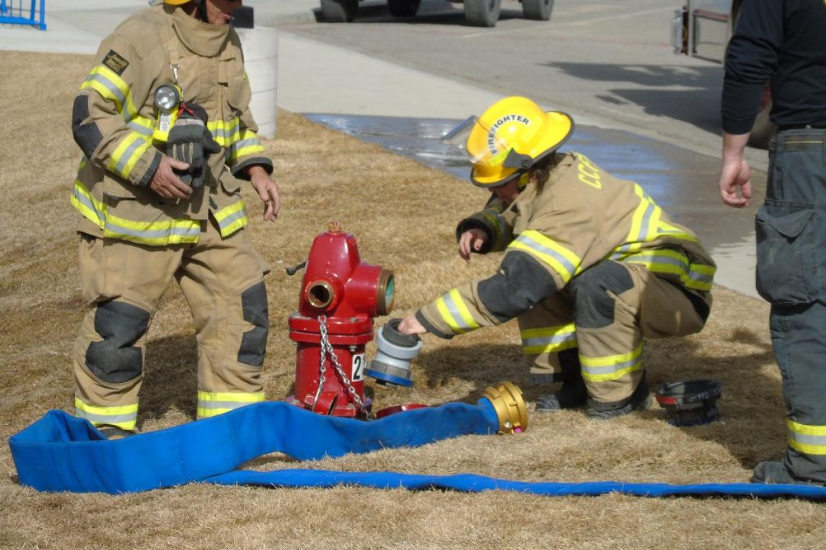 Firefighters attach hose to fire hydrant